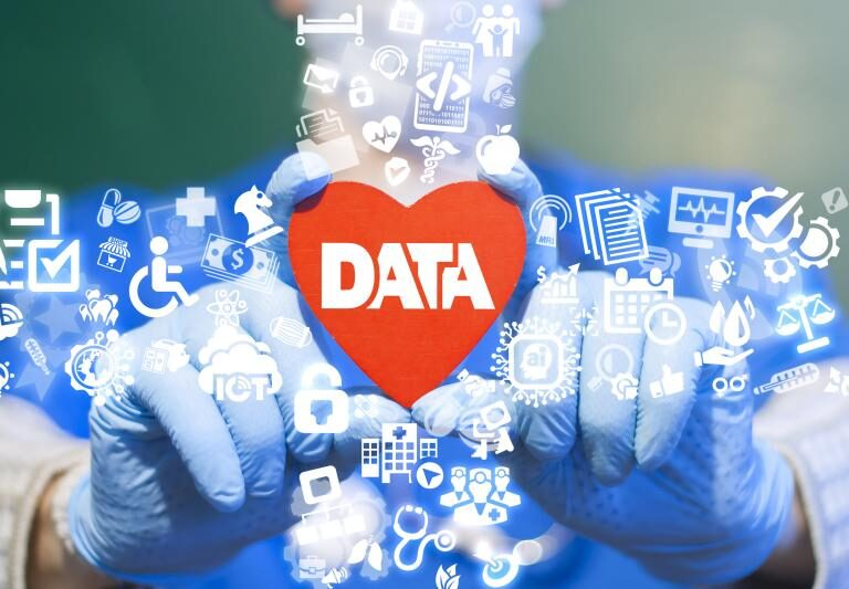 A heart with data and healthcare symbols over hands wearing surgical gloves.