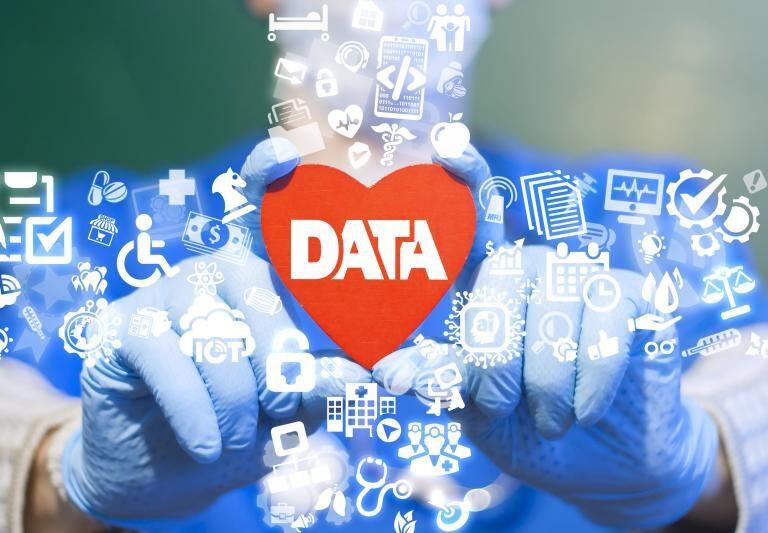 Un cœur avec des données et des symboles de soins de santé sur des mains portant des gants chirurgicaux.